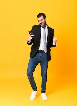 Het schot van gemiddelde lengte van de bedrijfsmens over geel met telefoon in overwinningspositie
