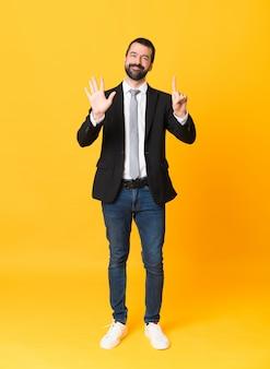Het schot van gemiddelde lengte van de bedrijfsmens over geïsoleerde geel die zes met vingers tellen