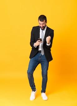 Het schot van gemiddelde lengte van de bedrijfsmens over geïsoleerde geel verrast en het verzenden van een bericht