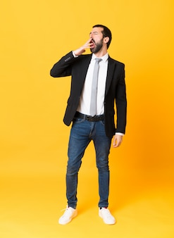 Het schot van gemiddelde lengte van de bedrijfsmens over geïsoleerde gele achtergrond die en wijd open mond geeuwen behandelen met hand