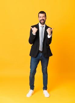 Het schot van gemiddelde lengte van de bedrijfsmens over geïsoleerde gele achtergrond met duimen op gebaar en het glimlachen