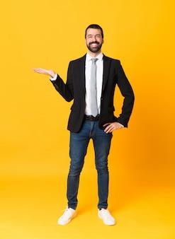 Het schot van gemiddelde lengte van de bedrijfsmens over gele holding copyspace denkbeeldig op de palm om een advertentie op te nemen