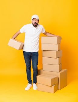 Het schot van gemiddelde lengte van de leveringsmens onder dozen over geïsoleerde geel met verrassingsuitdrukking