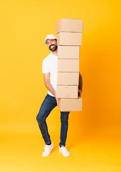 Het schot van gemiddelde lengte van de leveringsmens onder dozen over geïsoleerde geel