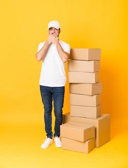 Het schot van gemiddelde lengte van de leveringsmens onder dozen over geïsoleerde gele achtergrond die mond behandelen met handen