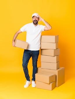 Het schot van gemiddelde lengte van de leveringsmens onder dozen over geïsoleerde gele achtergrond met verrassing en geschokte gelaatsuitdrukking