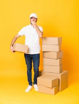 Het schot van gemiddelde lengte van de leveringsmens onder dozen over geïsoleerde gele bedekkende mond met handen