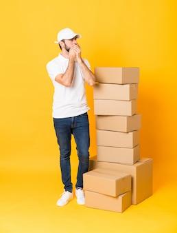 Het schot van gemiddelde lengte van de leveringsmens onder dozen over geïsoleerde gele muur die mond behandelen en aan de kant kijken