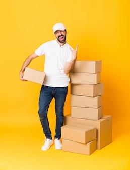 Het schot van gemiddelde lengte van de leveringsmens onder dozen over geïsoleerde gele muur die rotsgebaar maken