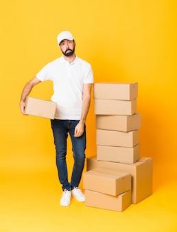 Het schot van gemiddelde lengte van de leveringsmens onder dozen over geïsoleerde gele muur met droevige en depressieve uitdrukking