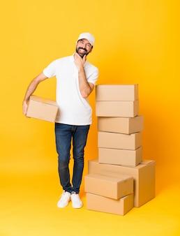 Het schot van gemiddelde lengte van de leveringsmens onder dozen over het geïsoleerde gele glimlachen als achtergrond