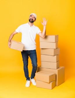 Het schot van gemiddelde lengte van de leveringsmens onder dozen over het geïsoleerde gele groeten met hand met gelukkige uitdrukking