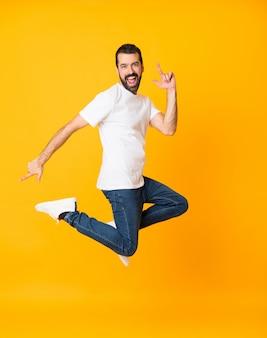 Het schot van gemiddelde lengte van de mens met baard die over geïsoleerde gele achtergrond springen