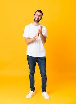 Het schot van gemiddelde lengte van de mens met baard over geïsoleerd geel het toejuichen na presentatie in een conferentie