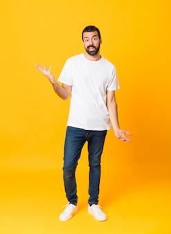 Het schot van gemiddelde lengte van de mens met baard over geïsoleerd geel makend twijfelgebaar