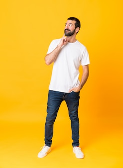 Het schot van gemiddelde lengte van de mens met baard over geïsoleerde geel denkend een idee terwijl omhoog het kijken