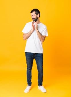 Het schot van gemiddelde lengte van de mens met baard over geïsoleerde gele achtergrond die iets plannen