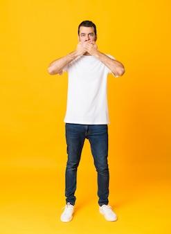 Het schot van gemiddelde lengte van de mens met baard over geïsoleerde gele achtergrond die mond behandelen met handen