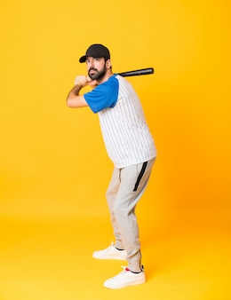 Het schot van gemiddelde lengte van de mens over geïsoleerd geel achtergrond speelhonkbal