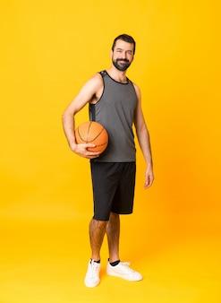 Het schot van gemiddelde lengte van de mens over geïsoleerd geel speelbasketbal