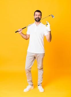 Het schot van gemiddelde lengte van de mens over geïsoleerd geel speelgolf die ok teken maken