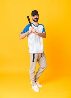 Het schot van gemiddelde lengte van de mens over geïsoleerd geel speelhonkbal als achtergrond
