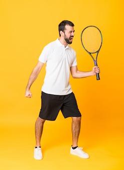 Het schot van gemiddelde lengte van de mens over geïsoleerd geel speeltennis en het vieren van een overwinning