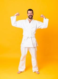 Het schot van gemiddelde lengte van de mens over geïsoleerde geel die karate doen en sterk gebaar maken
