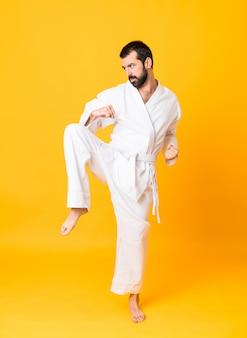 Het schot van gemiddelde lengte van de mens over geïsoleerde gele achtergrond die karate doet