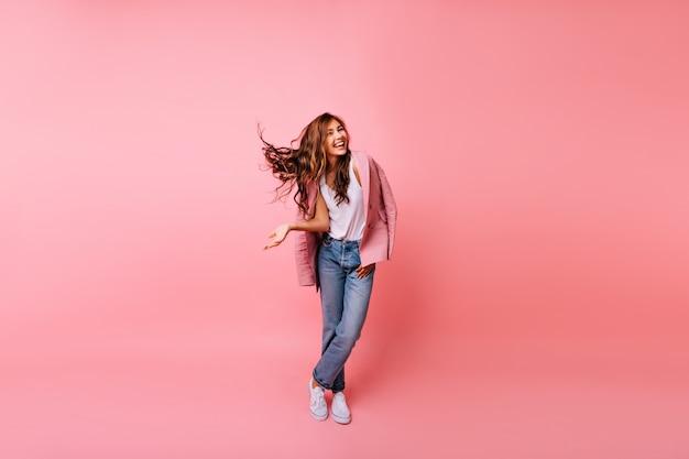 Het schot van gemiddelde lengte van de schitterende donkerharige dame die zich in zelfverzekerde houding bevindt. indoor portret van blij roodharig meisje in roze jasje en spijkerbroek.