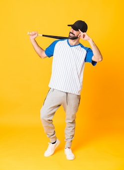 Het schot van gemiddelde lengte van een mens het spelen honkbal over geïsoleerde gele achtergrond