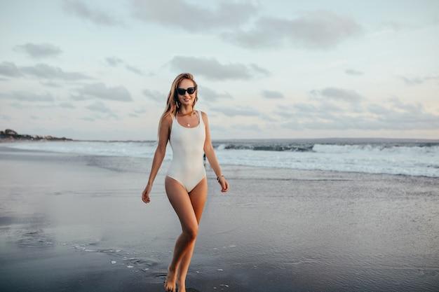 Het schot van gemiddelde lengte van enthousiaste vrouw in trendy zwempak die zich bij oceaankust bevinden. charmante gebruinde dame in witte badmode poseren met plezier op zeegezicht.