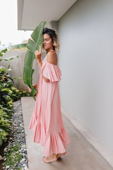 Het schot van gemiddelde lengte van het bevallige kaukasische meisje stellen met groene installatie. buiten foto van schattige blonde dame draagt een lange roze jurk.
