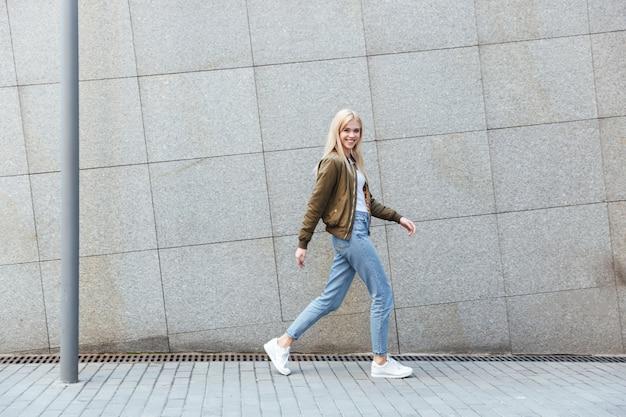 Het schot van gemiddelde lengte van het jonge vrouw lopen in de straat