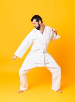 Het schot van gemiddelde lengte van het mandoing van karate over geïsoleerde gele achtergrond