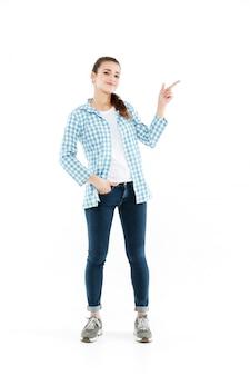 Het schot van gemiddelde lengte van jonge glimlachende jonge vrouw die bij exemplaarruimte toont