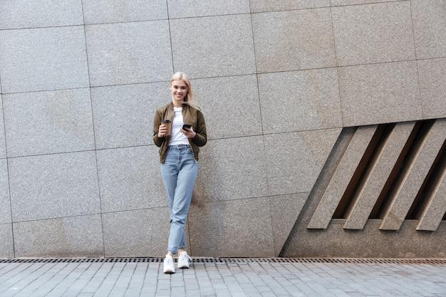 Het schot van gemiddelde lengte van jonge vrouw met kop van koffie en smartphone
