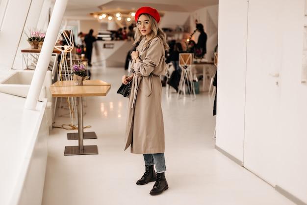 Het schot van gemiddelde lengte van krullende vrouw in beige lange geul en rode baret poseren in café