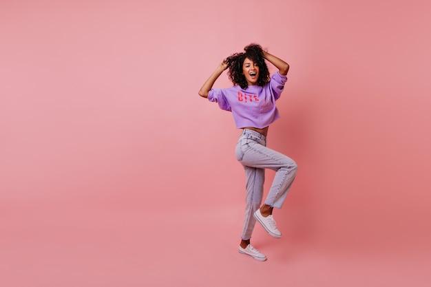 Het schot van gemiddelde lengte van modieuze vrouw die op rooskleurig danst. aantrekkelijk vrouwelijk model in jeans gek rond in studio.