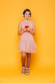 Het schot van gemiddelde lengte van mooi meisje gebruikend geïsoleerde hoofdtelefoons en smartphone