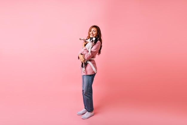 Het schot van gemiddelde lengte van schattig meisje dat in modieuze jeans franse buldog houdt. indoor portret van gelukkige langharige vrouw poseren met haar huisdier.