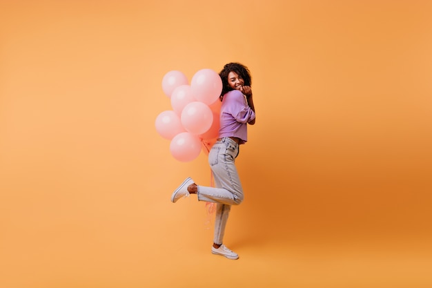 Het schot van gemiddelde lengte van verfijnd slank meisje dat zich op één been bevindt en ballons vasthoudt. lachen extatische zwarte vrouw dansen afterparty.