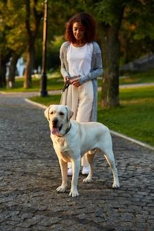 Het schot van gemiddelde lengte van vrij gezonde jonge dame die in de ochtend in park met hond loopt