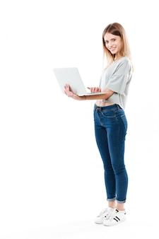 Het schot van gemiddelde lengte van vrouw die laptop computer met behulp van
