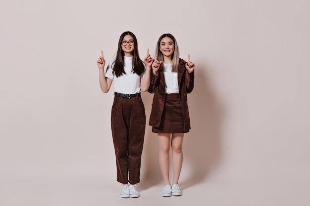 Het schot van gemiddelde lengte van vrouwen in bruine outfits die vingers tonen om voor tekst op geïsoleerde muur te plaatsen
