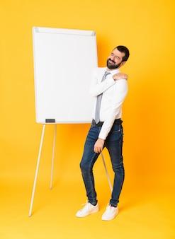 Het schot van gemiddelde lengte van zakenman die een presentatie op wit bord geven over geïsoleerde gele achtergrond die aan pijn in schouder lijden omdat ze zich hebben ingespannen