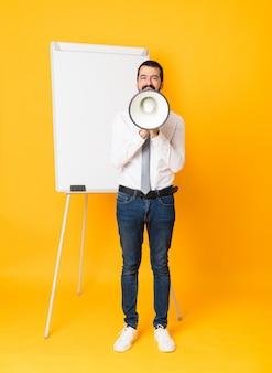 Het schot van gemiddelde lengte van zakenman die een presentatie op wit bord geven over geïsoleerde gele achtergrond die door een megafoon schreeuwt