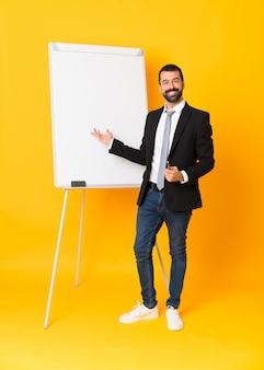 Het schot van gemiddelde lengte van zakenman die een presentatie op wit bord geven