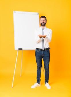 Het schot van gemiddelde lengte van zakenman die een presentatie op wit bord over geïsoleerde gele achtergrond geven die copyspace denkbeeldig op de palm houden om een advertentie op te nemen