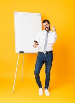 Het schot van gemiddelde lengte van zakenman die een presentatie op wit bord over geïsoleerde gele achtergrond met telefoon in overwinningspositie geven